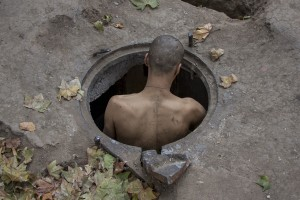 "A man called ""Bruce Lee"" and considered the boss of Gara de Nord, introduce himself in the sewer where he lives in Bucharest, Romania on November 6, 2011. During the winter hundreds of persons, sleep in the basement of the city to find heat."
