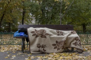 A woman sleeps on a bench near Gara de Nord in Bucharest, Romania on November 6, 2011. During the winter hundreds of persons, sleep in the basement of the city to find heat.