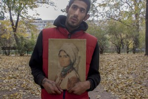 A drug addict man shows the reproduction of a Nicolae Grigorescu painting near Gara de Nord in Bucharest, Romania on November 6, 2011. During the winter hundreds of persons, sleep in the basement of the city to find heat.