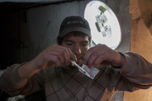 A man prepares a syringe of heroin in a sewer of Bucharest, Romania on November 12, 2011. During the winter hundreds of persons, sleep in the basement of the city to find heat.