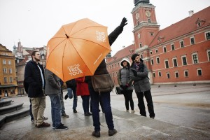 A tourist guide give explanations to a group of visitors at Plac Zamkowy in the historic center of Warsaw on February 13, 2014.