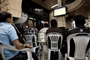People smoke hookah and watching a football match inside a bar of Tunis on October 16, 2012.