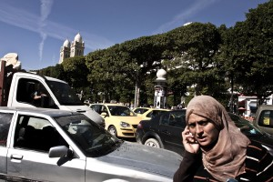 A woman talking on the phone while walking through the traffic of Avenue Bourguiba in Tunis on October 18, 2012.