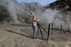 A man take a picture of fumaroles emerging from the Solfatara crater in Pozzuoli, Italy on April 12, 2014. Fumaroles are volcanic steam releases that contain sulfur causing a malodour similar to addle eggs.