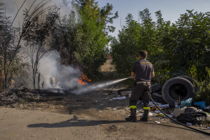 """A firefighter extinguishes a fire close to the farmlands of Afragola, Southern Italy on September 17, 2019. The area is part of the so-called """"land of fires"""", a site of toxic and illegal waste dump."""