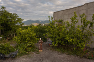 """May 23, 2015 – Terzigno, Italy: A statue of Padre Pio near a house located a few hundred meters from the Ranieri quarry. Ranieri quarry is an area of extraction of lava material disposed on June 5, 1995 with the establishment of the Vesuvius National Park. The landfill, which lies entirely in the Vesuvius National Park, despite the environmental constraints, in 2000 was used as a landfill with a promise to be """"cleaned up"""" within a year. Due to the loss of volume and the collapse of the waterproof membrane that covered the landfill at the quarry, it has turned into a lake of rainwater unhealthy where floating waste of all kinds."""