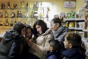 Marina Rinaldi in a bar shows some pictures to Rita (dx) and other firends of her in Rufoli, south Italy, on February 24, 2015. Marina Rinaldi is the first ex trans in the world to coach a soccer team.
