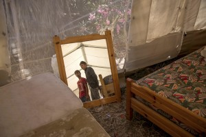 Pakistani migrants are reflected in a mirror inside a tent near an abandoned hotel where many migrants sleep in Kos island, Greece on June 8, 2015. Many migrants are continuing to arrive on the Greek Island of Kos from Turkey. The Island has recently seen a drop in tourist numbers which has been attributed to negative reports on the migrant crisis that is continuing to grip the area. Around 30,000 migrants have entered Greece so far in 2015, with the country calling for more help from its European Union counterparts.
