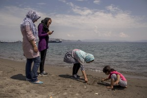 A migrant family from Syria play on a beach near the port in Kos island, Greece on June 8, 2015. Hundreds of migrants are continuing to arrive on the Greek Island from Turkey. The island has recently seen a drop in tourist numbers which has been attributed to negative reports on the migrant crisis that is continuing to grip the area. Around 30,000 migrants have entered the country so far this year, with the government calling for more help from its European Union counterparts.