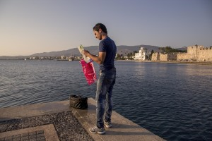 A Syrian migrant consults a map after being caught by the Greek Coast Guard teams in Kos island, Greece on June 14, 2015.