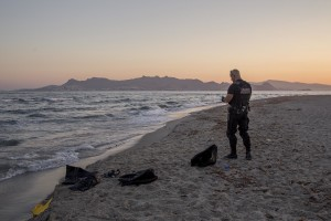 A policeman controls a beach after the arrival from the sea of Pakistani migrants in Kos island, Greece on June 15, 2015.