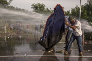 Hungarian riot police using a water cannon against protesting migrants on the Serbian side of the border in Horgos, Serbia on September 16, 2015. Hungary's border with Serbia has become a major crossing point into the European Union, with more than 160,000 access Hungary so far this year.