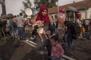 A woman flees with her children after Hungarian riot police using tear gases against protesting migrants on the Serbian side of the border, near Horgos in Serbia on September 16, 2015. Hungary's border with Serbia has become a major crossing point into the European Union, with more than 160,000 access Hungary so far this year.