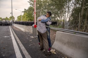 A man holds a syrian girl in front of the the Hungarian anti-riot police at the Serbian border with Hungary in Horgos, Serbia on September 16, 2015. Hungary's border with Serbia has become a major crossing point into the European Union, with more than 160,000 access Hungary so far this year.