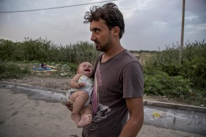 A man with his son near Tovarnik train station where migrants leave to Zagreb despite moves by Slovenia and Hungary to hold them back in Tovarnik, Croatia on September 19, 2015.