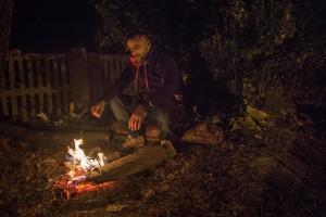 Tovarnik, Croatia: A migrant sits down beside fire after heavy rain at Tovarnik train station in Tovarnik, Croatia on September 20, 2015.