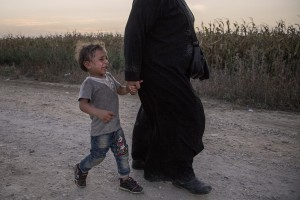 A mother carries her son who cries in a camp near the croatian border with Serbia in Tovarnik, Croatia on September 17, 2015.