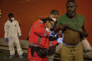 "A doctor of Italian Red cross visits a migrant after the arrival of the Norwegian ship ""Siem Pilot Stavanger"" with 810 refugees at Manfredi pier of Salerno port in Salerno on August 2, 2016. The ship carrying migrants coming mostly from Sudan, Nigeria, Syria and Egypt."