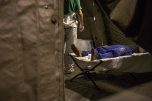 "A migrant in poor health is seen inside a tent of Italian Red cross after the arrival of the Norwegian ship ""Siem Pilot Stavanger"" with 810 refugees at Manfredi pier of Salerno port in Salerno on August 2, 2016. The ship carrying migrants coming mostly from Sudan, Nigeria, Syria and Egypt."