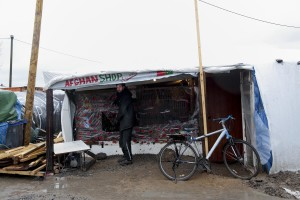 "January 27, 2016 – Calais, France: A migrant is seen outside an Afghan shop in the migrants camp of Calais, known as ""The Jungle"". While migrants have for years sought to cross over to Britain from Calais, the numbers have shot up since the refugee crisis went into overdrive last year."