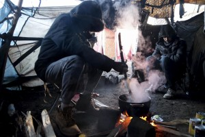 "January 28, 2016 – Calais, France:  Migrants cook inside their home in the refugee camp of Calais, known as ""The Jungle"". While migrants have for years sought to cross over to Britain from Calais, the numbers have shot up since the refugee crisis went into overdrive last year."