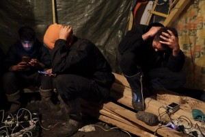 "January 29, 2016 – Grande-Synthe, France: Migrants recharge their phones in a tent of Grande-Synthe refugee camp near Dunkirk, northern France, known as ""The Jungle 2″. Around 3,000 refugees and migrants of Kurdish descent from Iraq and Syria live in the camp."