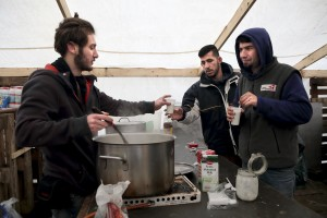 "January 29, 2016 – Grande-Synthe, France: Migrants get tea by a volunteer in a tent of the refugee camp of Grande-Synthe near Dunkirk, northern France, known as ""The Jungle 2″. Around 3,000 refugees and migrants of Kurdish descent from Iraq and Syria live in the camp."