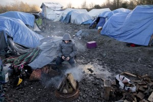 "January 30, 2016 – Grande-Synthe, France: A migrant gets warm near a fire inside the refugee camp of Grande-Synthe near Dunkirk, northern France, known as ""The Jungle 2″. Around 3,000 refugees and migrants of Kurdish descent from Iraq and Syria live in the camp."