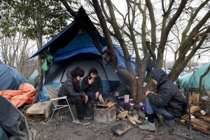 "January 29, 2016 – Grande-Synthe, France: Migrants get warm near a fire inside the refugee  camp of Grande-Synthe near Dunkirk, northern France, known as ""The Jungle 2″. Around 3,000 refugees and migrants of Kurdish descent from Iraq and Syria live in the camp."