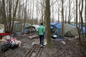"January 29, 2016 – Grande-Synthe, France: A migrant walks inside the refugee camp of Grande-Synthe near Dunkirk, northern France, known as ""The Jungle 2."" Around 3,000 refugees and migrants of Kurdish descent from Iraq and Syria live in the camp."