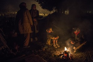 Migrants warm near a fire at refugee camp along the border of Greece and Macedonia near the town of Idomeni in Greece on March 18, 2016. The refugees are being stopped from moving beyond Greece and have been languishing in the rain, mud, and cold with insufficient food and medical care while sleeping in small tents.