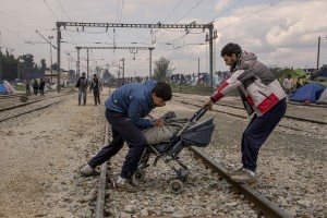 "Migrants carry a stroller containing firewood at the Idomeni refugee camp in Idomeni, Greece on March 17, 2016. Refugees' ""journey of hope"" towards Western European countries where they dream of having a better life ends in the Balkans following the latest agreement between EU and Turkey."