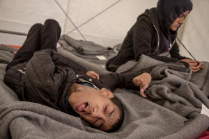Ibrahim Nagiami, 18 years old from Aleppo, Syria is seen on his bed in a tent of the makeshift camp at the Greek-Macedonian border, near the Greek village of Idomeni where thousands of migrants are stranded by the Balkan border blockade in Idomeni, Greece on March 20, 2016. Ibrahim has mental and physical disabilities (probably he has been suffering of spastic tetraparesis) since his birth, but after the outbreak of war in Syria, his condition deteriorated because of continuous bombing, his father says.