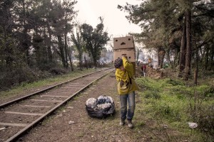 "March 18, 2016 – Idomeni, Greece: A refugee child carries boxes containing firewood at the Idomeni refugee camp in Idomeni, Greece on MArch 18, 2016. Refugees' ""journey of hope"" towards Western European countries where they dream of having a better life ends in the Balkans following the latest agreement between EU and Turkey."