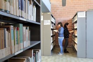 """March 2, 2016 – Naples, Italy: Schoolgirls consult books inside the municipal public library """"Domenico Severino"""" in Scampia."""
