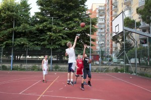 """June 8, 2016 – Naples, Italy: Boys playing basketball inside """"Corto Maltese"""" park in Scampia district. Since three years a group of citizens called """"Pollici Verdi"""" take care of """"Corto Maltese"""" pak and self-tax with about 10 euro per month each, with the goal of saving the municipal gardens from degradation."""