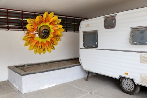 """February 24, 2016 – Naples, Italy: A paper sunflower close to the entry of """"Officina delle Culture"""". On each of the sunflower petal is marked the name of one of the green areas recovered by the association """"Volontari per Napoli"""" in Scampia district. """"Officina delle culture"""" is a multi-purpose center born in the Neapolitan neighborhood of Scampia and dedicated to Gelsomina Verde, an innocent victim of Camorra. The site is run by the association """"Resistenza Anticamorra"""" and its objective is to offer concrete alternatives to children at risk but also to prisoners who have no restrictive measures."""