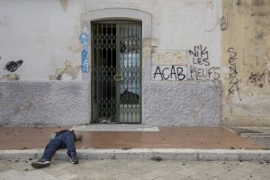 LECCE, ITALY – NOVEMBER 13: A migrant rests on the ground outside the train station of Lecce where a lot of migrants sleep during the night, because of the lack of facilities that could accommodate them in Puglia, Southern Italy on November 13, 2016.
