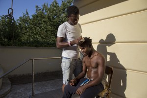 "July 19, 2016 – Naples, Italy: A migrant get a haircut by a friend inside ""Villa Chianese"", a C.A.S. (Extraordinary Reception Center) in Chiaiano, near Naples, southern Italy. CAS are imagined in order to compensate the lack of places inside ordinary reception center in case of substantial arrivals of migrants."