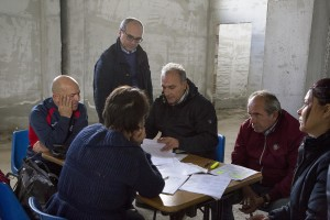 """Salvatore Madonna (sx) gets the documents of his new accommodation after the transfer from his old apartment inside the """"vele"""" of Scampia, in Naples on November 11, 2016. The """"vele"""" of Scampia, become famous for the long and bloody Camorra feuds, will be demolished starting from spring 2017."""