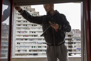 """A man at work inside an apartment in the """"Vele"""" of Scampia, during the transfer of a family into one of the new accommodations realized always in Scampia, in Naples on November 11, 2016. The """"vele"""" of Scampia, become famous for the long and bloody Camorra feuds, will be demolished starting from spring 2017."""