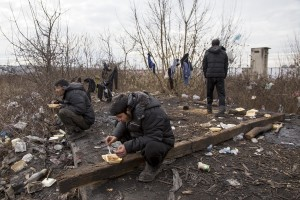 Migrants sit eating their lunch outside an abandoned warehouse where they took refuge in Belgrade, Serbia on February 3, 2017. Hundreds of migrants have been sleeping in freezing conditions in central Belgrade looking for ways to cross the heavily guarded EU borders.
