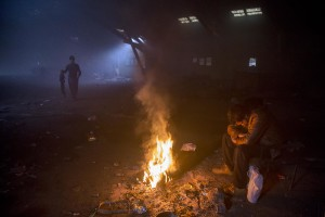 A migrant sits around a fire to warm himself from the cold in an abandoned warehouse in Belgrade, Serbia on February 3, 2017. Hundreds of migrants have been sleeping in freezing conditions in downtown Belgrade looking for ways to cross the heavily guarded EU borders.