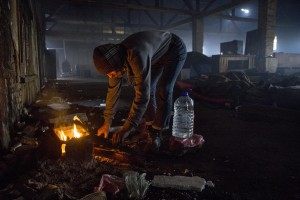 A migrant warms up around a fire in an abandoned warehouse in Belgrade, Serbia on February 4, 2017. Hundreds of migrants have been sleeping in freezing conditions in downtown Belgrade looking for ways to cross the heavily guarded EU borders.