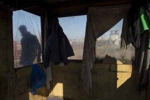 A migrant is seen through the window of a cabin built outside an abandoned warehouse where he and other migrants took refuge in Belgrade, Serbia on February 5, 2017. Hundreds of migrants have been sleeping in freezing conditions in central Belgrade looking for ways to cross the heavily guarded EU borders.