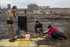 Refugees shower outside an abandoned warehouse where they took refuge in Belgrade, Serbia on February 3, 2017. Hundreds of migrants have been sleeping in freezing conditions in central Belgrade looking for ways to cross the heavily guarded EU borders.