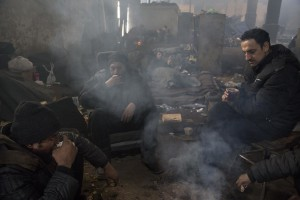 Migrants sit drinking a tea inside an abandoned warehouse where they took refuge in Belgrade, Serbia on February 4, 2017. Hundreds of migrants have been sleeping in freezing conditions in central Belgrade looking for ways to cross the heavily guarded EU borders.