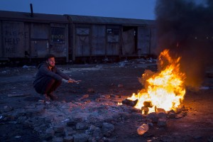 A migrant sits around a fire to warm himself from the cold outside an abandoned warehouse in Belgrade, Serbia on February 3, 2017. Hundreds of migrants have been sleeping in freezing conditions in downtown Belgrade looking for ways to cross the heavily guarded EU borders.