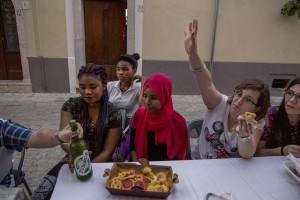Locals and beneficiaries of the protection systems for asylum seekers and refugees are seen during a dinner organized in the center of Petruro Irpino, southern Italy on June 14, 2017. Petruro Irpino is an Italian small village with 367 inhabitants in the province of Avellino in Campania, which is claiming to be an efficient model of integration and where people of different religions and coming from different parts in the world peaceful live together.