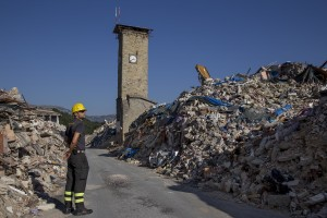 A firefighter walks among the rubble inside the red zone almost one year after the earthquake in the village of Amatrice, central Italy on August 1, 2017. Italy was struck by a powerful 6.2 magnitude earthquake in the night of August 24, 2016 which has killed at least 297 people and devastated dozens of houses in the Lazio village of Amatrice and other Amatrice fractions.